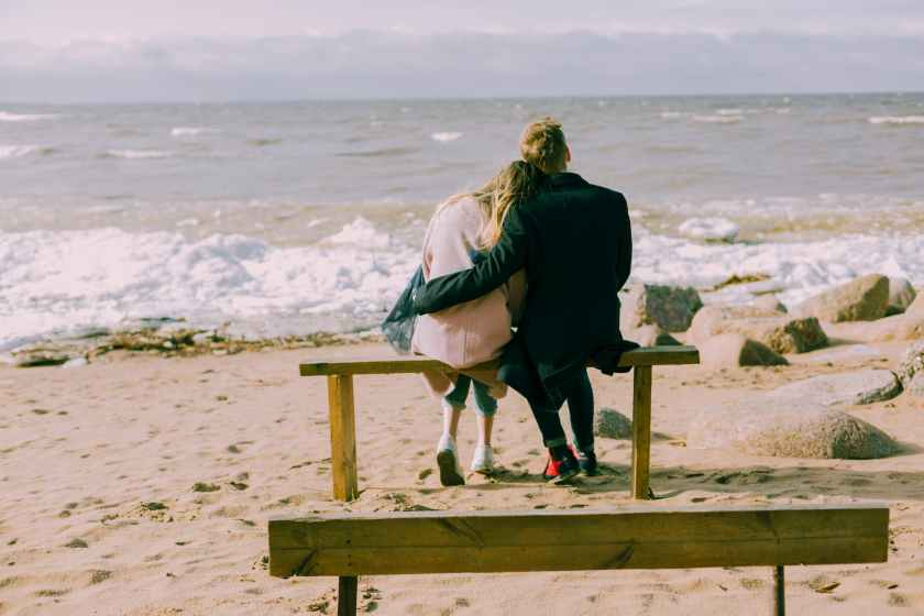 man and woman hugging and sitting on a bench